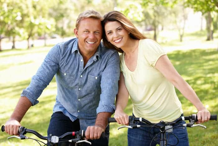 Happy middle-aged couple on bikes