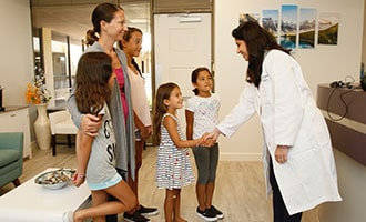 Dr. Bhave greeting children to the office
