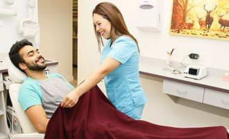 Staff putting blanket on patient